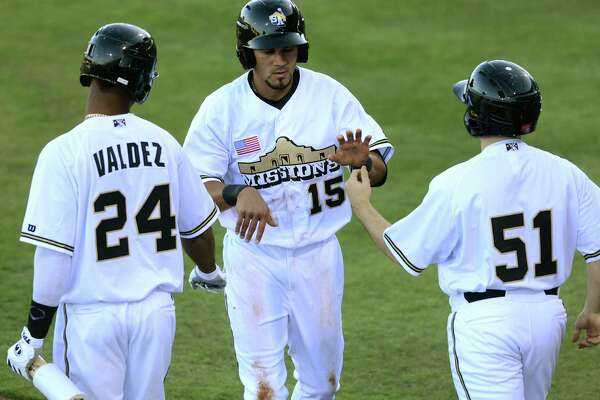 Reymond Fuentes (15) of the San Antonio Missions is greeted by teammates Jeudy Valdez (24) and the batboy after scoring the first run of the season during Texas League action at Nelson Wolff Stadium on Thursday, April 4, 2013.