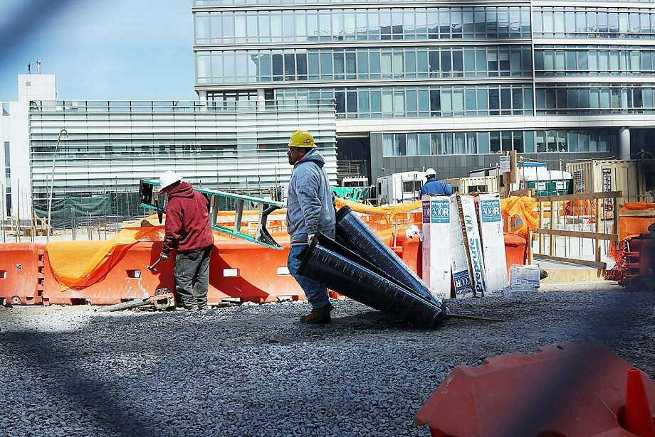 NEW YORK, NY - APRIL 04: People work on a construction site near the old Domino Sugar factory in the rapidly developing neighborhood of Williamsburg on April 4, 2013 in the Brooklyn borough of New York City. Two Trees management, which owns the closed Domino Sugar factory, has unveiled new plans for the site that will include more than half a million square feet of office space, 228,000 square feet of open space and 2,284 apartments and retail space. The plan is a continuation of the rapid development of the Williamsburg waterfront which offers Manhattan views and water taxis to other parts of New York City.  (Photo by Spencer Platt/Getty Images) Photo: Spencer Platt, Getty Images