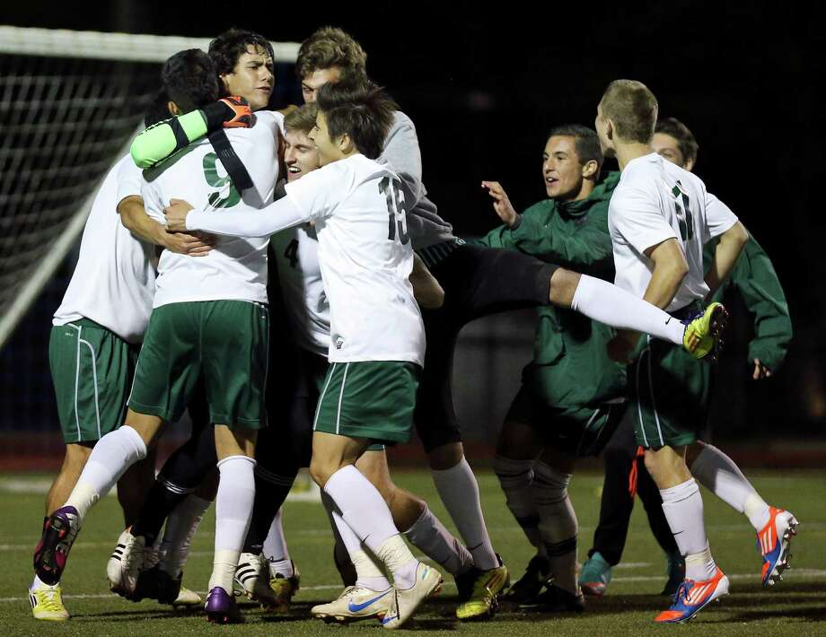 Reagan's goalie Diego Flores (left center) celebrates with teammates after defeating Steele in a shootout during their Class 5A second round playoff game Thursday April 4, 2013 at Orem Stadium. Reagan won the shootout 5-3. Photo: Edward A. Ornelas, Express-News / © 2013 San Antonio Express-News