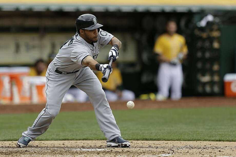 Seattle Mariners' Robert Andino bunts the ball against the Oakland Athletics, advancing runners to second and third base in the fifth inning of a baseball game Thursday, April 4, 2013, in Oakland, Calif. (AP Photo/Ben Margot) Photo: Ben Margot, Associated Press