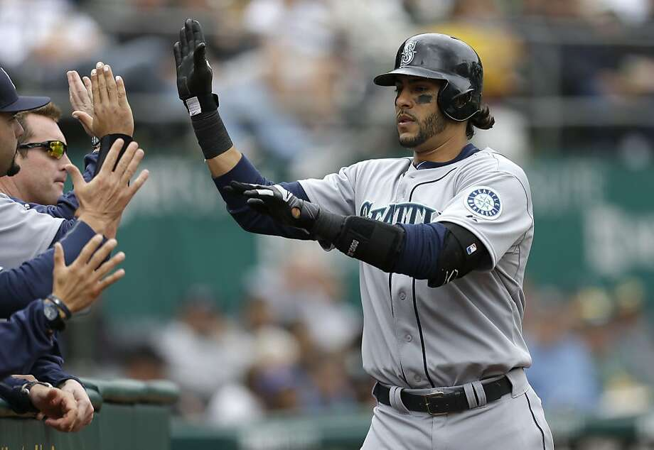 Seattle Mariners' Michael Morse, right, is congratulated after hitting a home run off Oakland Athletics' A.J. Griffin in the sixth inning of a baseball game Thursday, April 4, 2013, in Oakland, Calif. (AP Photo/Ben Margot) Photo: Ben Margot, Associated Press