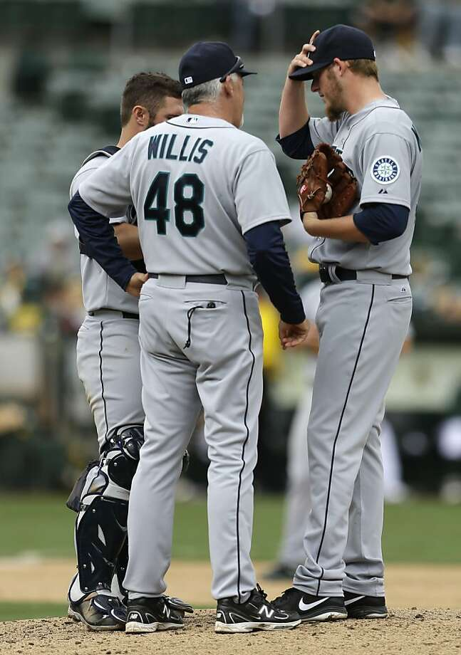 Seattle Mariners Brandon Maurer, right, is visited on the mound by pitching coach Carl Willis in the sixth inning of a baseball game against the Oakland Athletics Thursday, April 4, 2013, in Oakland, Calif. (AP Photo/Ben Margot) Photo: Ben Margot, Associated Press