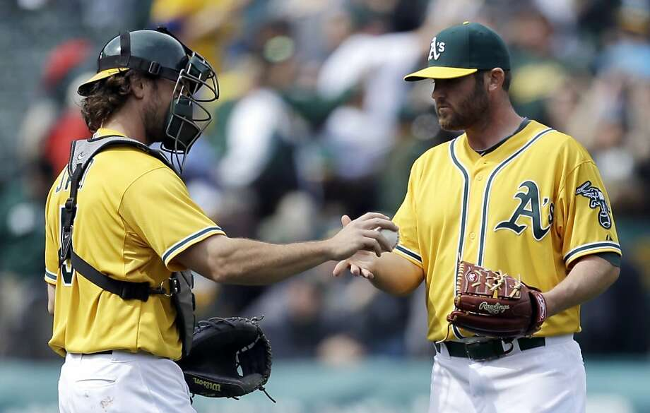 Oakland Athletics' John Jaso, left, hands the game ball to pitcher Ryan Cook at the end of a baseball game against the Seattle Mariners, Thursday, April 4, 2013, in Oakland, Calif. (AP Photo/Ben Margot) Photo: Ben Margot, Associated Press