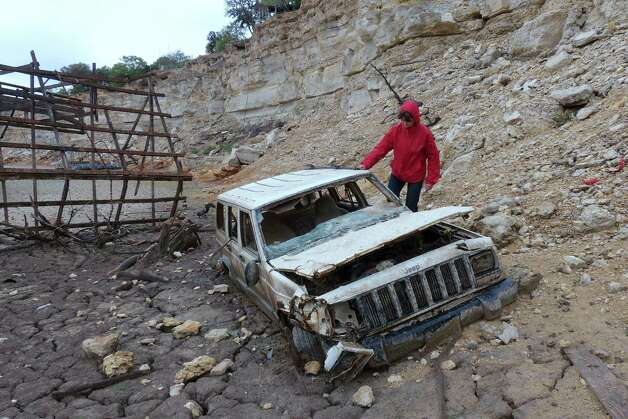 Karen Ripley, a resident of the Medina Lake area, investigates a Jeep that the receding waters have left exposed at Elm Cove on Wednesday, April 3, 2013. Photo: Billy Calzada, San Antonio Express-News / San Antonio Express-News