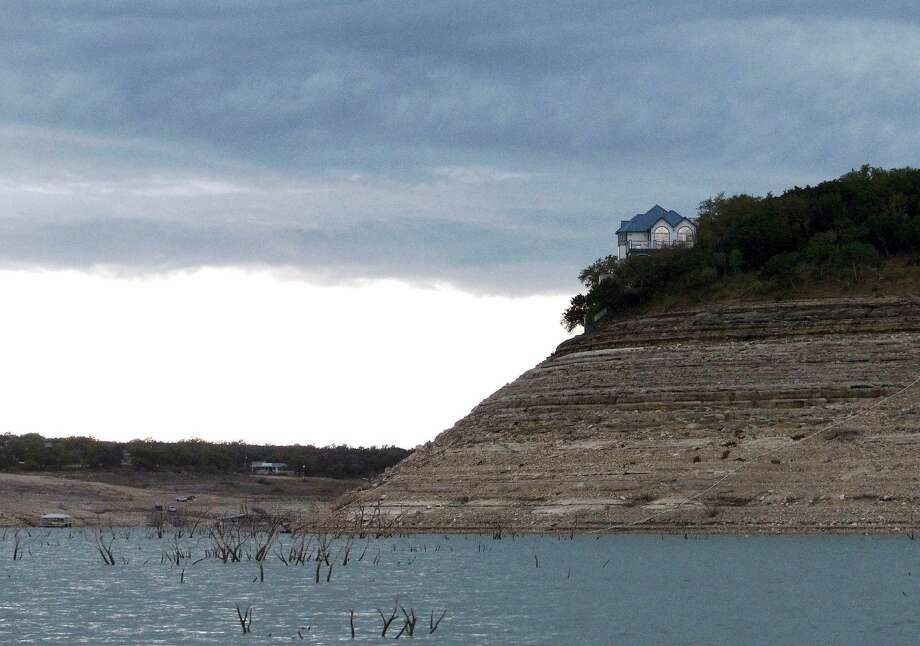 A lakeside home stands far above the receding waters of Medina Lake, which has dropped to 6.5 percent of capacity on Wednesday, April 3, 2013. Photo: Billy Calzada, San Antonio Express-News / San Antonio Express-News