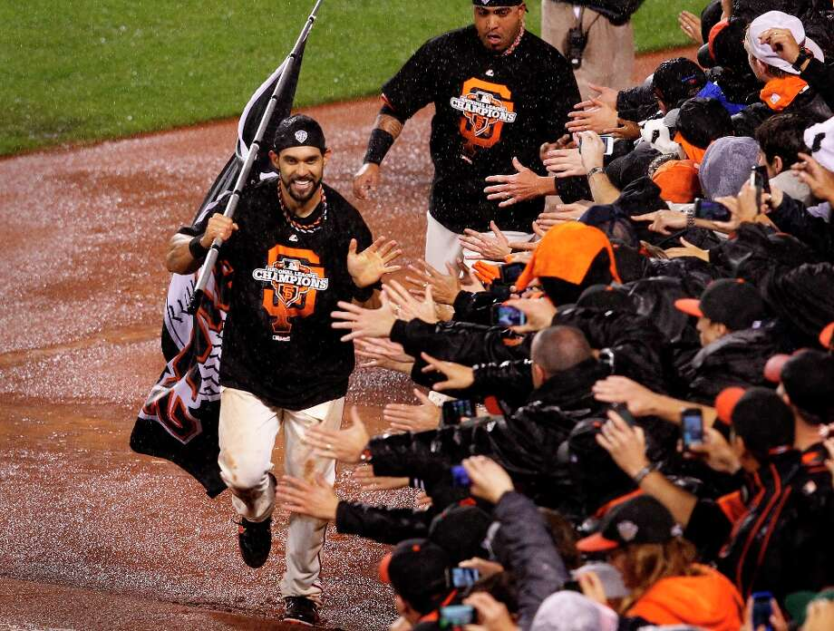 Angel Pagan and another Giant ran along the right field wall greeting fans. The San Francisco Giants defeated the St. Louis Cardinals 9-0 to win the National League pennant Monday October 22, 2012 at AT&T park. Photo: Brant Ward, The Chronicle / ONLINE_YES