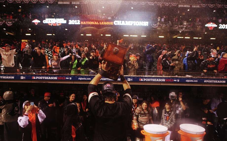 Brandon Crawford displays the NLCS trophy to fans after the San Francisco Giants\' victory in Game 7 of the NLCS  over the St. Louis Cardinals at AT&T Park Monday, October 22, 2012 in San Francisco, Calif. Photo: Pete Kiehart, The Chronicle / ONLINE_YES