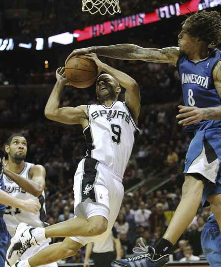Spurs' Tony Parker gets blocked by Minnesota Timberwolves' Michael Beasley (08) at the AT&T Center on Friday, Dec. 3, 2010. Spurs defeated the Timberwolves, 107-101. Kin Man Hui/kmhui@express-news.net Photo: KIN MAN HUI, SAN ANTONIO EXPRESS-NEWS / kmhui@express-news.net