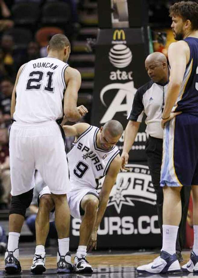 Memphis Grizzlies' Marc Gasol, of Spain, right, and referee Olandis Poole, middle right, watch as San Antonio Spurs' Tony Parker, of France, is helped up by Spurs' Tim Duncan, left, after suffering a left calf injury during the first half of an NBA basketball game, Sunday, Feb. 27, 2011, in San Antonio. Photo: AP