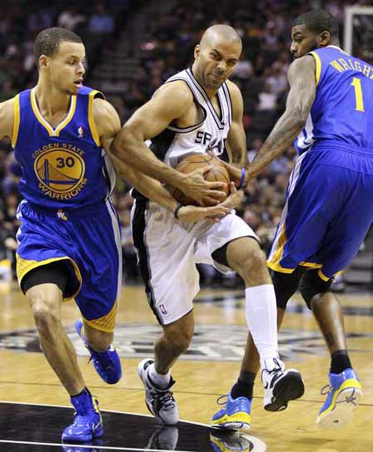 FOR SPORTS - Spurs' Tony Parker looks for room between  Warriors' Stephen Curry (left) and Warriors' Dorell Wright during first half action Monday March 21, 2011 at the AT&T Center.  (PHOTO BY EDWARD A. ORNELAS/eaornelas@express-news.net) Photo: EDWARD A. ORNELAS, SAN ANTONIO EXPRESS-NEWS / SAN ANTONIO EXPRESS-NEWS NFS