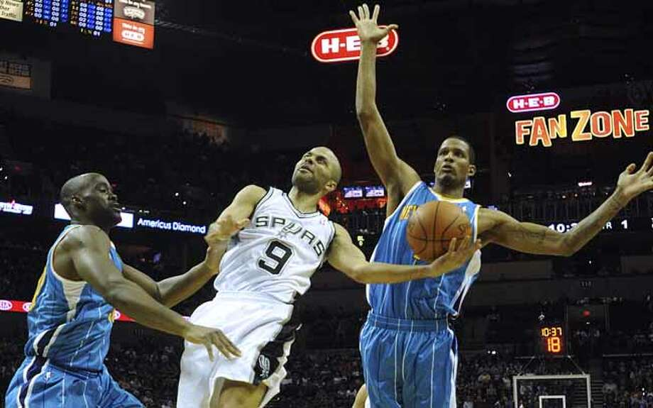 Tony Parker of the San Antonio Spurs (9) shoots a layup as Emeka Okafor, left, of the New Orleans Hornets, and Trevor Ariza, right, defend on Thursday, Feb. 2, 2012.  Billy Calzada / San Antonio Express-NewsNew Orleans Hornets at San Antonio Spurs Photo: Billy Calzada, San Antonio Express-News / San Antonio Express-News