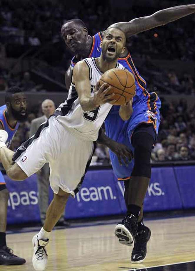 SPORTS   Spurs guard Tony Parker twists under Kendricks Perkins for a bucket in the first half as the San Antonio Spurs play the Oklahoma City Thunder at the AT&T Center  on February 4, 2012 Tom Reel/ San Antonio Express-News Photo: TOM REEL, San Antonio Express-News / San Antonio Express-News