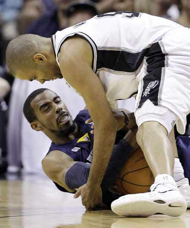 Memphis Grizzlies' Mike Conley, bottom, and San Antonio Spurs' Tony Parker, top, of France, scramble for control of the ball during the first quarter of an NBA basketball game on Thursday, April 12, 2012, in San Antonio. Photo: AP