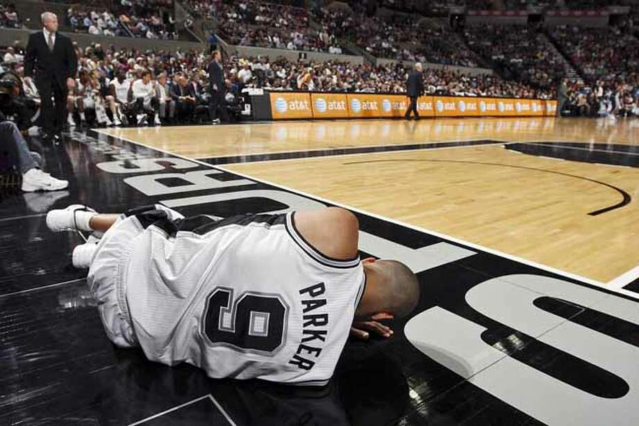 FOR SPORTS - San Antonio Spurs' Tony Parker lies on the floor after getting fouled by Memphis Grizzlies' Gilbert Arenas during first half action Thursday April 12,  2012 at the AT&T Center. Photo: EDWARD A. ORNELAS, SAN ANTONIO EXPRESS-NEWS / © SAN ANTONIO EXPRESS-NEWS (NFS)