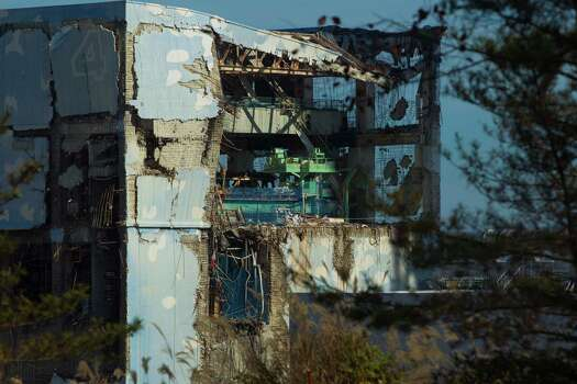 In this Nov. 12, 2011 file photo, the Unit 4 reactor building of the crippled Fukushima Dai-ichi nuclear power station is seen through a bus window in Okuma, Japan, when the media were allowed into Japan's tsunami-damaged nuclear power plant for the first time since the March 11 disaster. Japan's tsunami-hit Fukushima power plant remains fragile nearly a year after it suffered multiple meltdowns, its chief said Tuesday, March 6, 2012, with makeshift equipment, some mended with tape, keeping crucial systems running. (AP Photo/David Guttenfelder, Pool, File) Photo: David Guttenfelder, Associated Press / AP Pool