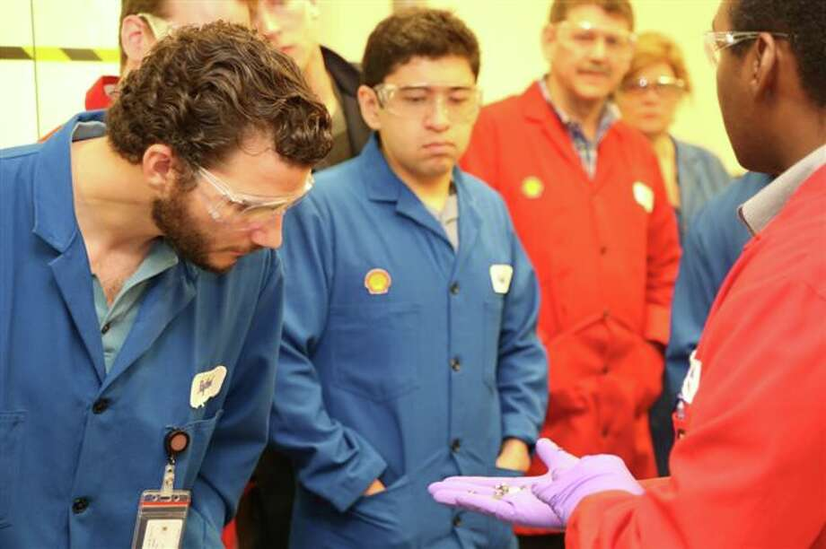 Shell scientist David Dudek (rear) looks on as University of Houston engineering students check out how lab instruments measure and quantify fuel lubricity. Photo: Shell