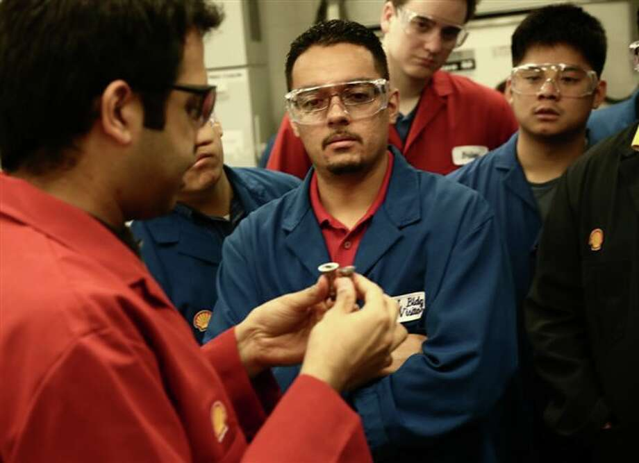 Shell scientist Vinod Natarajan shows University of Houston engineering students gasoline fuel injector tips, used in a Shell lab. Photo: Shell