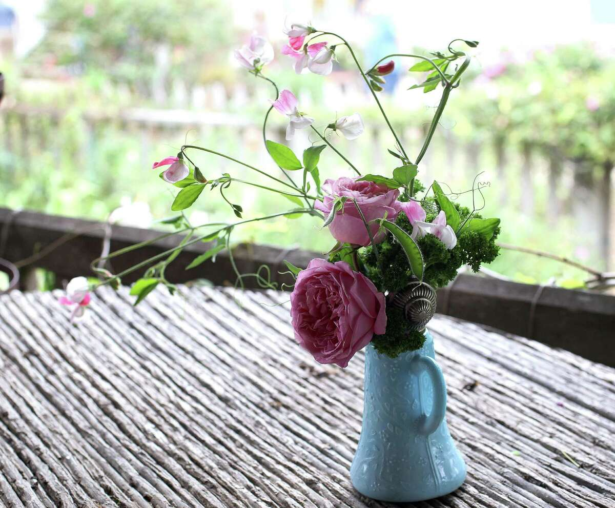 An antique syrup pitcher with parsley, sweet peas and rose blooms is a floral idea for Mother's Day.
