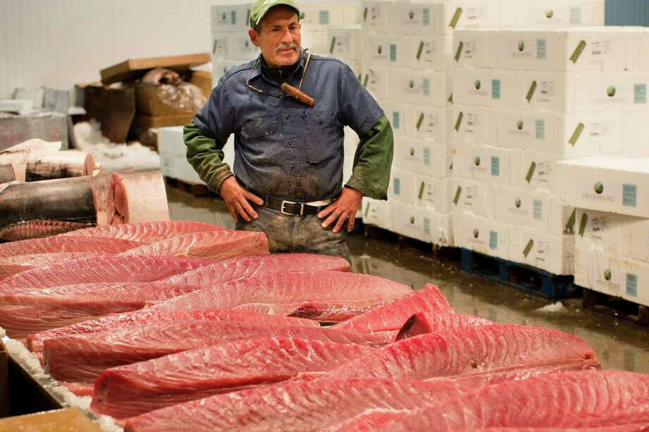 A fishmonger stands beside a table of newly sectioned fish at the Fulton Fish Market, Friday, March 29, 2013, in New York. The Fulton Fish Market, located in the Hunts Point neighborhood of the Bronx, is the world's largest after Tokyo. In this football-field size refrigerated building, time and money is measured in thousand-dollar pieces of salmon whose price-for-quality is negotiated on the spot. The product goes to the buyer instantly and is trucked to restaurants or retail vendors. Photo: John Minchillo, AP / FR170537 AP