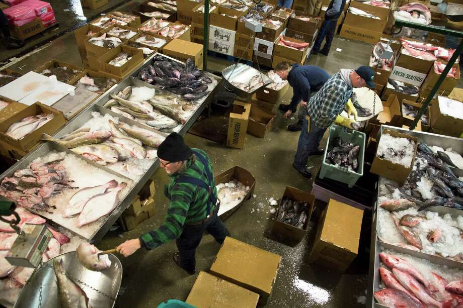 Fishmongers ply their trade on the floor of the Fulton Fish Market, Friday, March 29, 2013, in New York. The Fulton Fish Market, located in the Hunts Point neighborhood of the Bronx, is the world's largest after Tokyo. In this football-field size refrigerated building, time and money is measured in thousand-dollar pieces of salmon whose price-for-quality is negotiated on the spot. The product goes to the buyer instantly and is trucked to restaurants or retail vendors. Photo: John Minchillo, AP / FR170537 AP