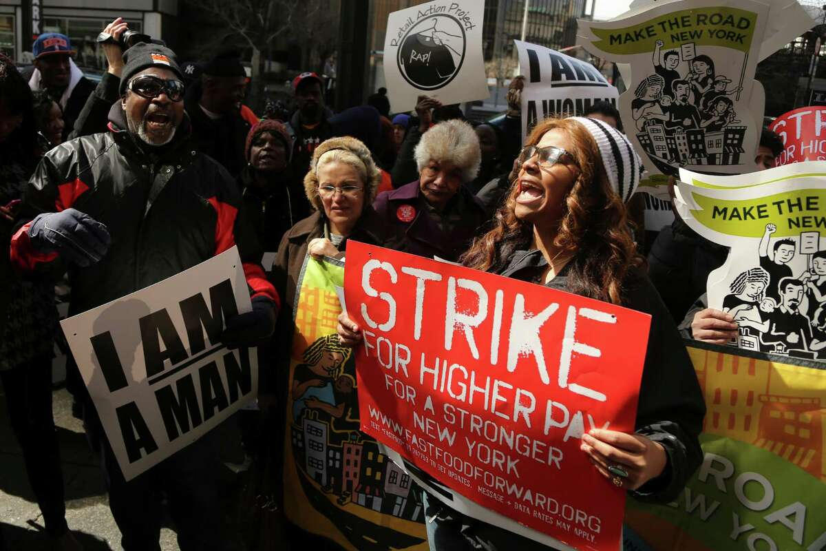Demonstrators holds a sign and chant slogans outside of a Wendy's fast food restaurant, Thursday, April 4, 2013 in New York. New York City fast food workers plan a second job action day to press for higher wages. Organizers say hundreds of workers plan to demonstrate Thursday at dozens of fast food establishments, including McDonald's, Domino's, Wendy's and Pizza Hut.