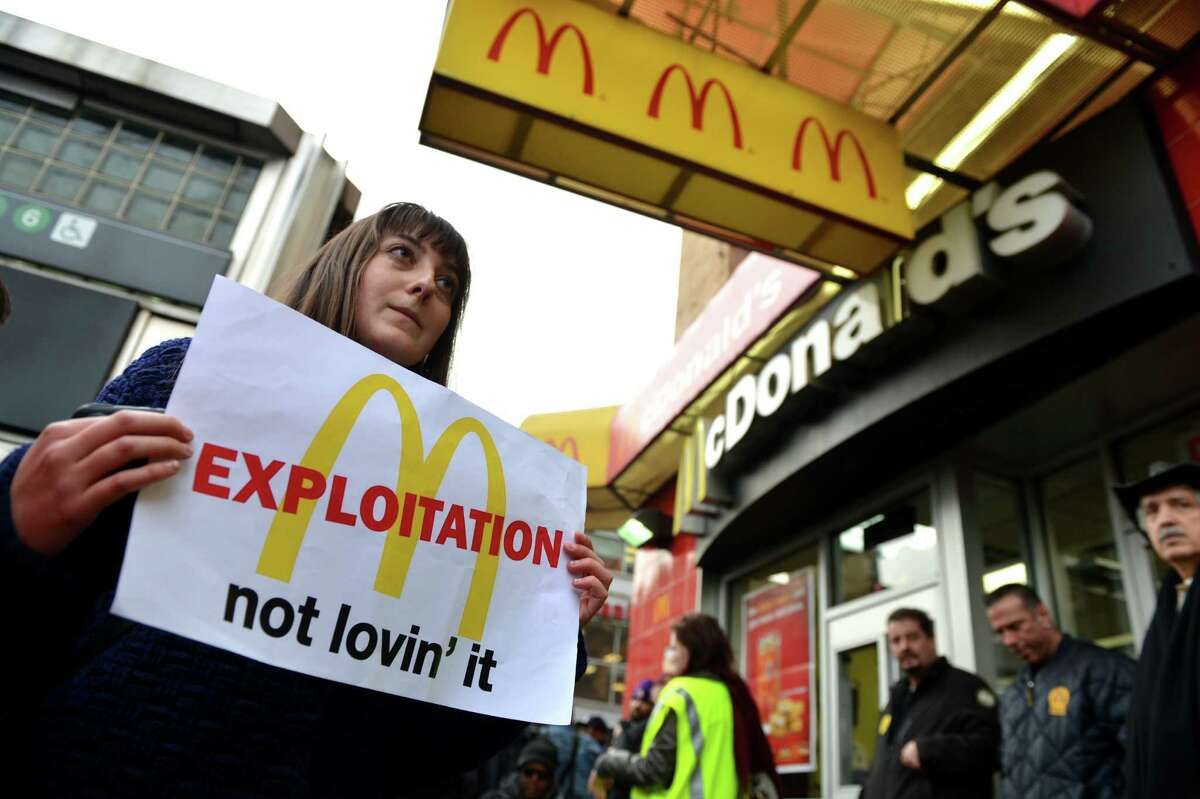 A woman carries a sign past a McDonald's on East 125th Street and Lexington Avenue in Harlem during a protest by fast food workers and supporters for higher wages April 4, 2013 in New York. AFP PHOTO/Stan HONDASTAN HONDA/AFP/Getty Images