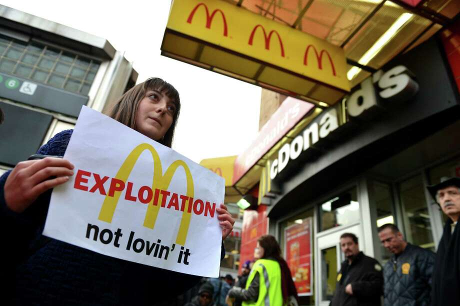 A woman carries a sign past a McDonald's on East 125th Street and Lexington Avenue in Harlem during a protest by fast food workers and supporters for higher wages April 4, 2013 in New York. AFP PHOTO/Stan HONDASTAN HONDA/AFP/Getty Images Photo: STAN HONDA, AFP/Getty Images / AFP