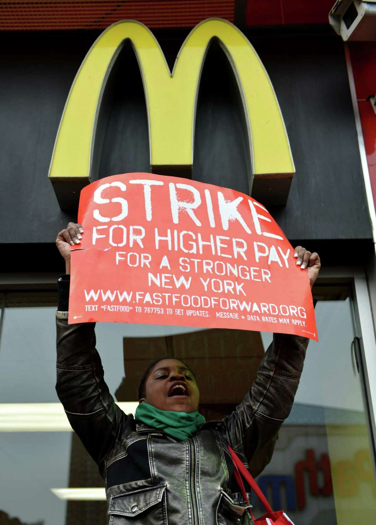 Tara Waring carries a sign in front of a McDonald's on East 125th Street and Lexington Avenue in Harlem during a protest by fast food workers and supporters for higher wages April 4, 2013 in New York. AFP PHOTO/Stan HONDASTAN HONDA/AFP/Getty Images