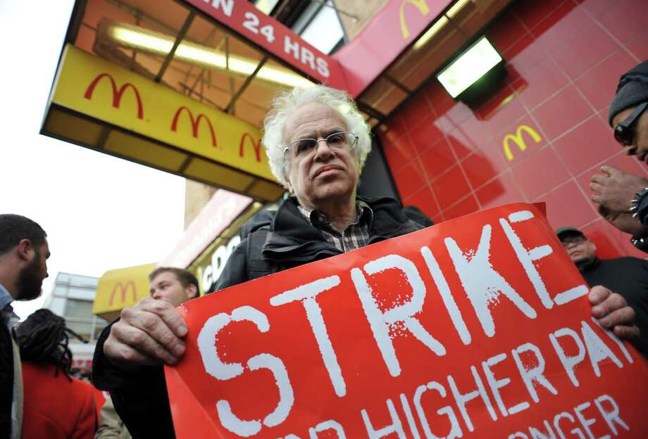 A man carries a sign in front of a McDonald's on East 125th Street and Lexington Avenue in Harlem during a protest by fast food workers and supporters for higher wages April 4, 2013 in New York. AFP PHOTO/Stan HONDASTAN HONDA/AFP/Getty Images Photo: STAN HONDA, AFP/Getty Images / AFP