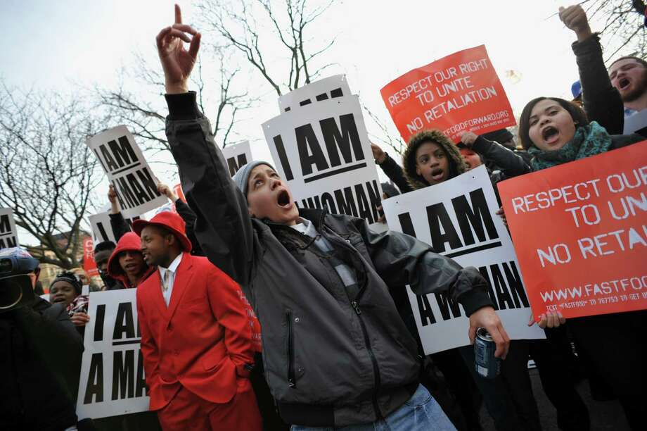 """People rally at Marcus Garvey Park in Harlem during a protest by fast food workers and supporters for higher wages April 4, 2013 in New York. The protest was held on the 45th anniversary of the assasination of civil rights leader Martin Luther King, Jr., the """"I Am A Man"""" sign replicates one displayed at a rally led by King. AFP PHOTO/Stan HONDASTAN HONDA/AFP/Getty Images Photo: STAN HONDA, AFP/Getty Images / AFP"""