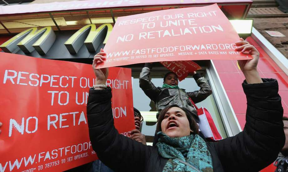 NEW YORK, NY - APRIL 04:  People hold signs during a protest for better wages for fast food workers outside a McDonald's restaurant in Harlem on April 4, 2013 in New York City. Organizers said hundreds of fast food workers were expected to walk off the job today from establishments including Wendy's, McDonald's and KFC to rally for better pay and union rights. Photo: Mario Tama, Getty Images / 2013 Getty Images