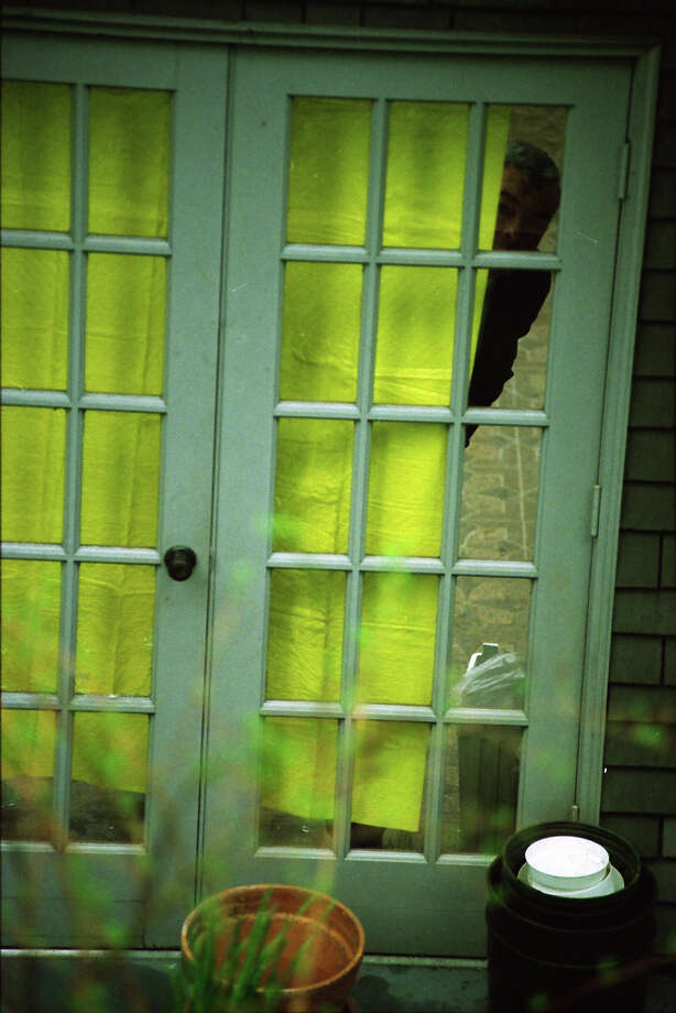 A investigator looks out from the greenhouse where Kurt Cobain's body was found, April 8, 1994. Photo: Mike Urban/Copyright MOHAI, Seattle Post-Intelligencer Collection, 2000.107_19940408_0082.