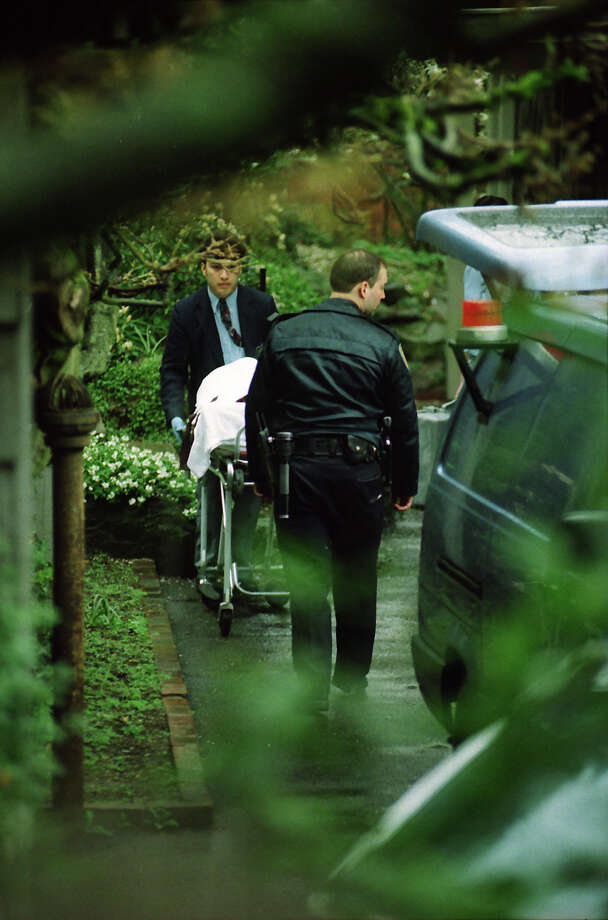 The body of Kurt Cobain is taken to a medical examiner's van after it was removed from his home, April 8, 1994. This full frame has not previously been published. Photo: Phil H. Webber/Copyright MOHAI, Seattle Post-Intelligencer Collection, 2000.107_19940408_0093.