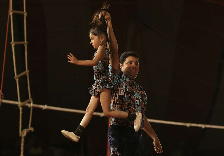 Entertainment or abuse?An acrobat lifts a girl by her hair during a local circus in Lahore, Pakistan. Photo: K.M. Chaudary, Associated Press