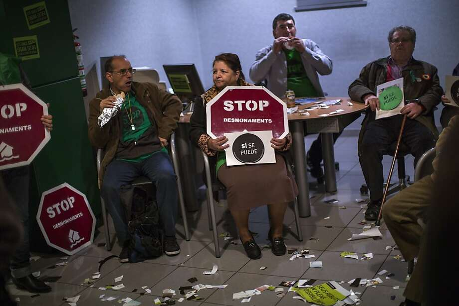Stop! In the name of lunch … In Barcelona, members of the Mortgage Victims' Platform eat sandwiches as they occupy a Bankia bank branch in support of neighbors who have been evicted from their homes. Photo: Emilio Morenatti, Associated Press