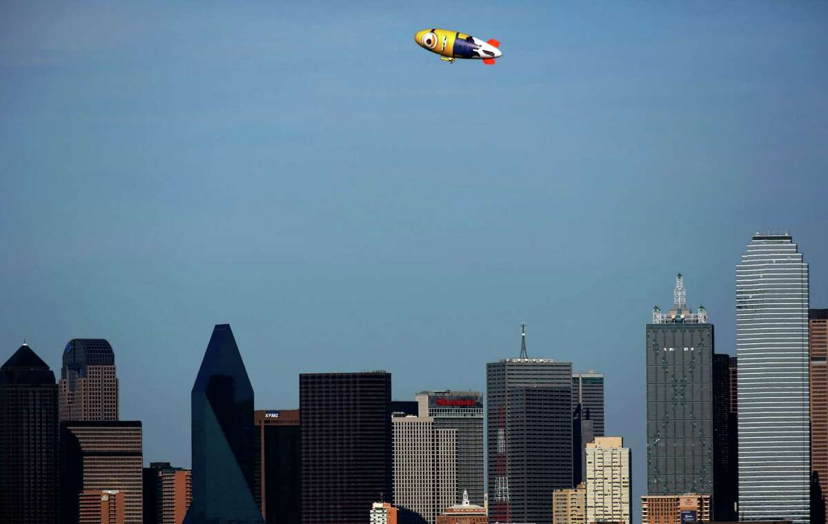 """It's a bird, It's a plane...No, It's Despicablimp! The blimp depicting a giant yellow Minion passes over downtown Dallas, April 1, 2013. It's in town to promote the upcoming release of """"Despicable Me 2"""" on July 3, 2013. The A-150 blimp is one of the largest in the world at 165 feet long, 55 feet high and 46 feet wide. (Tom Fox/The Dallas Morning News)"""