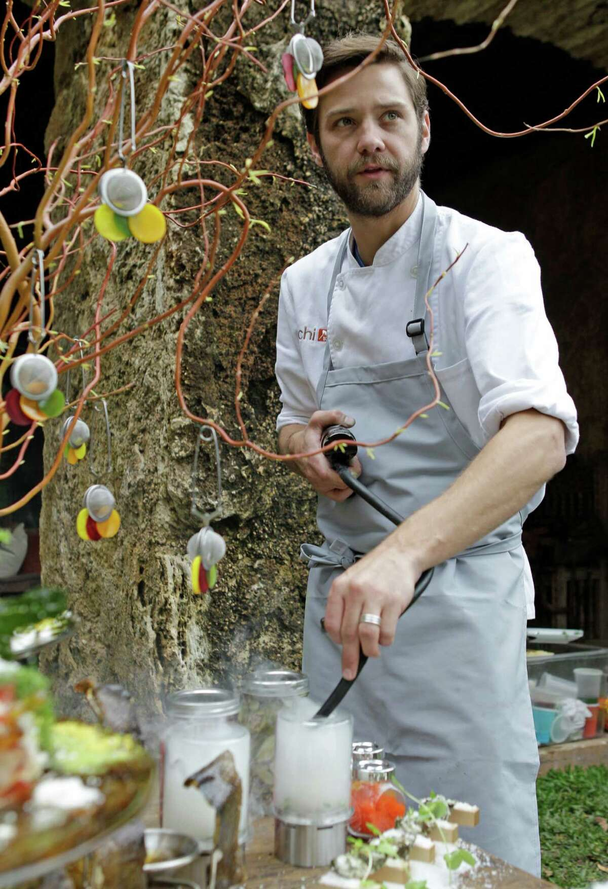 """Uchi chef Kaz Edwards adds rosemary smoke to a dish of egg yolk with salmon eggs and grilled asparagus in preparation for """"Feast: A Dinner Series,"""" inspired by the exhibition """"Feast: Radical Hospitality in Contemporary Art"""" at Blaffer Art Museum."""