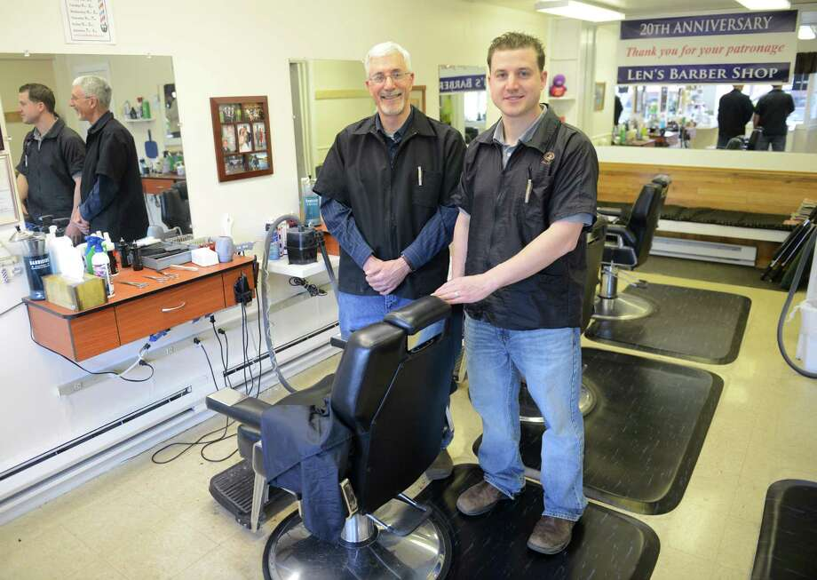Store owner Len Kennan, left, and his son, Chris Kennan, pose for a photo inside Len's Barber Shop in New Milford, Conn. on Friday, April 5, 2013.  The family shop, run by Len Kennan and his son, Chris Kennan, recently celebrated its 20th anniversary. Photo: Tyler Sizemore / The News-Times