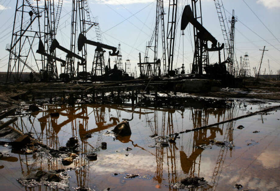 Oil derricks are reflected in a polluted puddle on the shore of the Caspian Sea just outside the capital Baku in 2005. Photo: Mladen Antonov, AFP/Getty Images