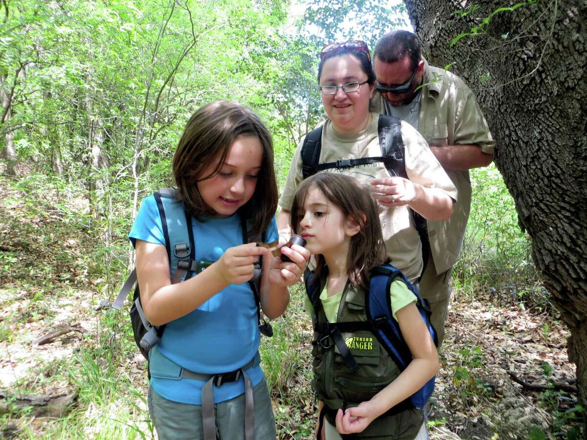 Aurora Stevens, 7 (left), and her sister Nayely, 6, open the geocache they just found and read the coordinates written on a scrap of paper to find the next location in their treasure hunt. Mom Wendy Stevens looks on as dad James Stevens prepares to enter the new latitude and longitude into his hand-held GPS unit.