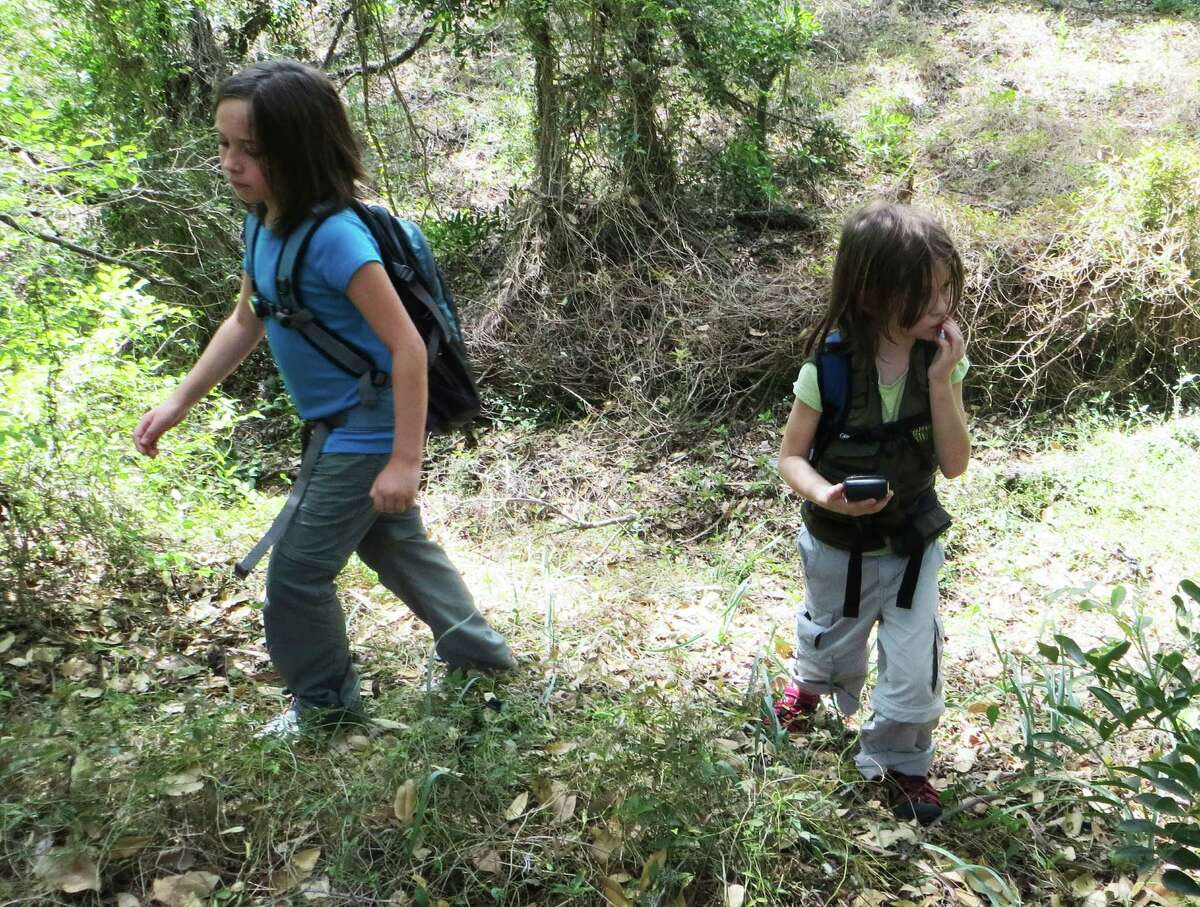 Aurora and Nayely Stevens search for the next geocache in Olmos Basin Park. With their parents, teachers Wendy and James Stevens, the girls go geocaching almost every weekend.