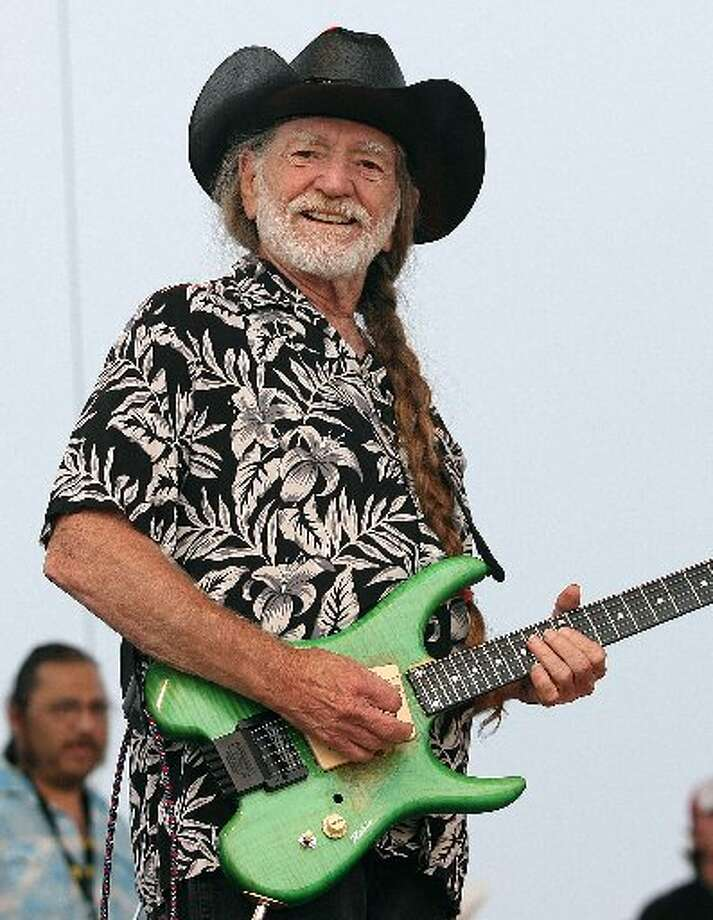 Bright green Willie: Nelson's battered acoustic guitar Trigger gets the day off as he opts for an electric guitar at Willie's Fourth of July Picnic in Fort Worth in 2006. Photo: Getty Images