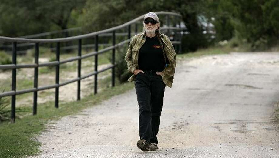 A walk with Willie: Nelson walks down his driveway to join independent gubernatorial candidate Kinky Friedman for a news conference in Spicewood, Texas, in 2006. Photo: Getty Images