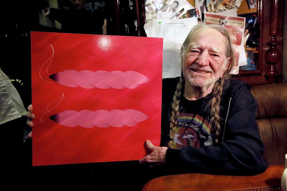 Art collector Willie: Nelson holds a painting that conveys his thoughts on the subjects of marijuana and gay marriage in the spring of 2013. Should it prove too cryptic: He's in favor of both. Photo: Gary Miller, Getty Images / 2013 Gary Miller