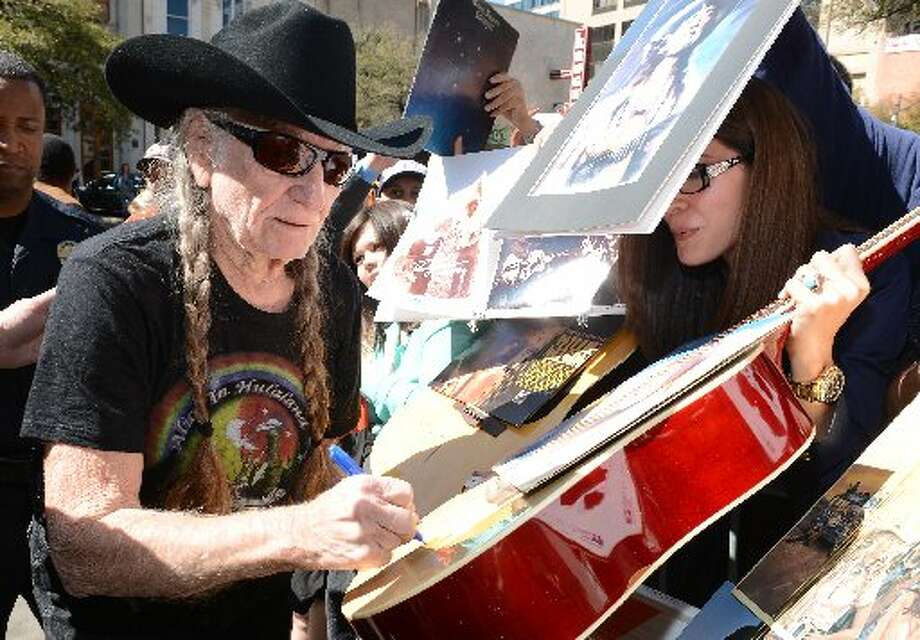 Fan-friendly Willie: Nelson has played a lot of guitar. He's also signed a lot of autographs. In 2004 he required carpal tunnel surgery. Photo: Getty Images