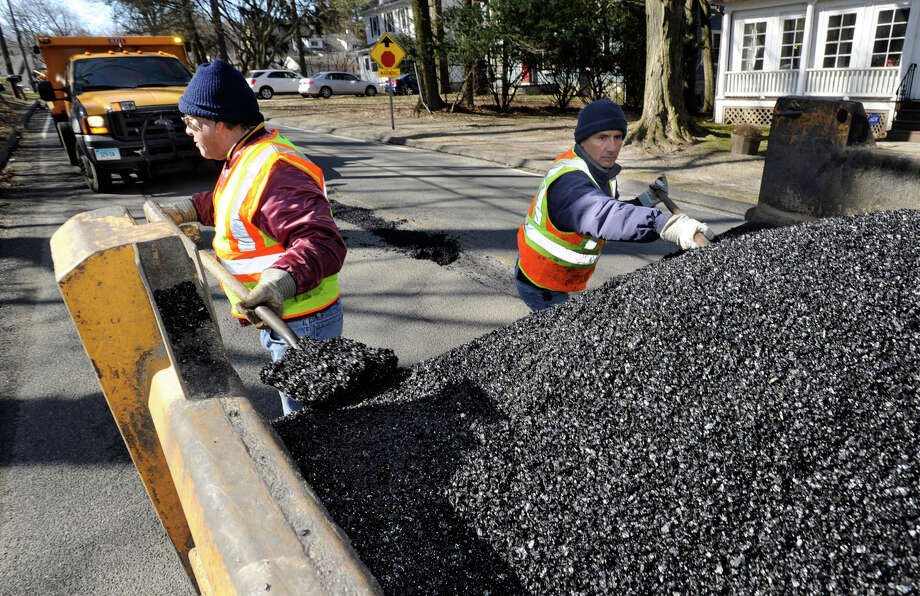 Larry Michael, left, and Walter Garcia, employees of the Danbury Highway Department, fill potholes on West Wooster Street in Danbury, Conn., Monday, April 2, 2013. Photo: Carol Kaliff / The News-Times