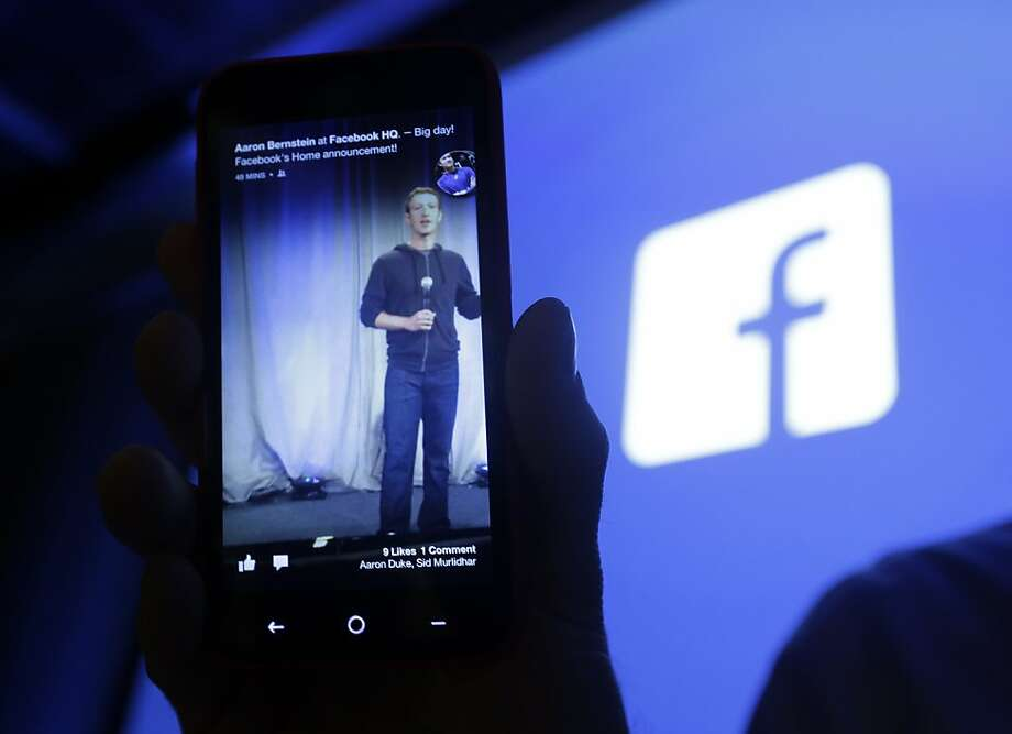 Michael Goodwin, senior partner for HTC, displays an HTC First smartphone with the new Facebook interface - showing a photo of Facebook CEO Mark Zuckerberg - at Facebook headquarters in Menlo Park. Photo: Marcio Jose Sanchez, Associated Press