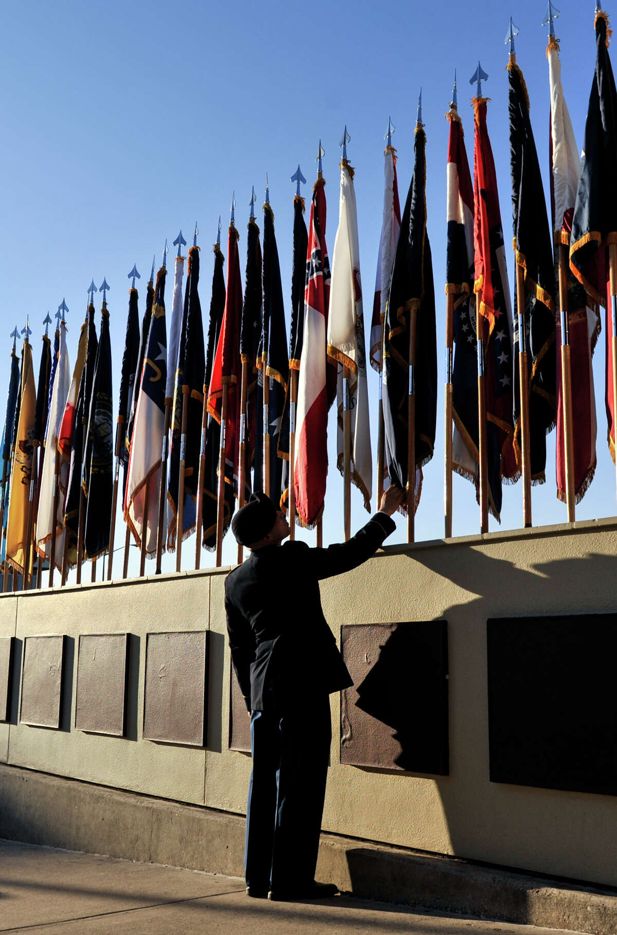 PFC Brandon Backner inspects flags at the entry to Arthur MacArthur Parade Field at Fort Sam Houston prior to the Relinquishment of Command Ceremony Friday.
