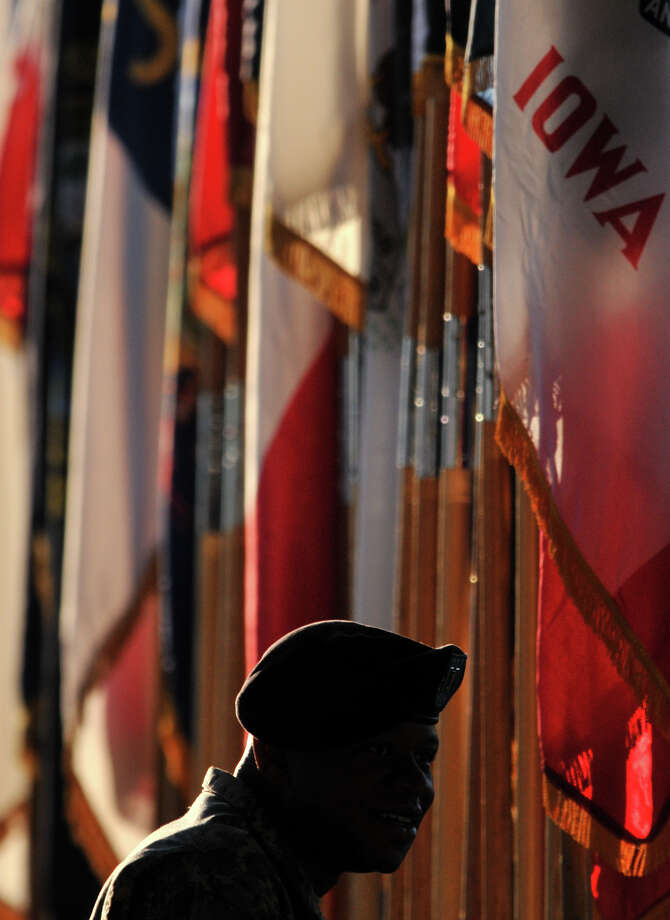 Capt. Preston Roy is silhouetted against flags and early morning light prior to the Relinquishment of Command Ceremony at the U.S. Army Medical Department Center and School at Fort Houston on Friday. Photo: Robin Jerstad
