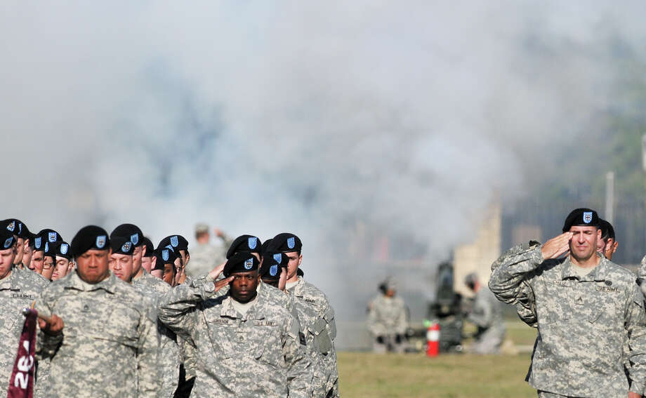 Troops listen to a 21-gun salute as it was fired during the Relinquishment of Command Ceremony at Fort Sam Houston's Arthur MacArthur Parade ground Friday. Photo: Robin Jerstad